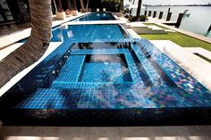 This dazzling perimeter-overflow pool and spa features Lightstreams Glass Tile in Peacock Blue. Aquatic Consultants, Inc./Brian Van Bower; STA Architectural Group; Photographer: Matthew Pace http://www.luxurypools.com/builders-designers/aquatic-consultants-inc-brian-van-bower.aspx