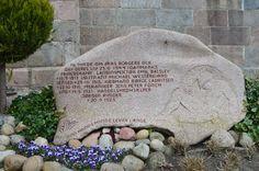 Foto April 2016, Års kirke - Øst for kirken står en mindesten over faldne modstandsfolk (1940-45) fra Aars Sogn. På kirkegårdens afd. E, kan man se gravminderne for de faldne modstandsfolk. På gravstenene er der påsat en bronzeplade til minde om deres indsats for Danmark under besættelsen.