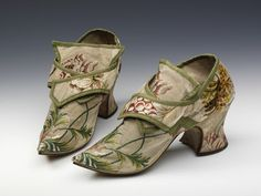 This pair of women's shoes is made up of a brocaded silk woven in Spitalfields, London. Indoor shoes for women were usually made of patterned silk although it was very rare for them to match the fabric of the gown worn with them. The shoes have a fashionable pointed toe, a medium stocky heel and latchets that would have been fastened with buckles. Buckles were regarded as separate accessories and transferred from one pair of shoes to another.