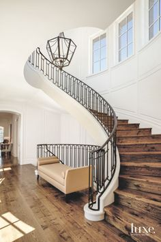 Exposed wood beams, a barn-style door from real Carriage door Company and stone walls surrounding the winding staircase— crafted by Ravenhill Construction—resonate with the home's setting. The Heritage Timber Ddition floors are from duChâteau. Stairs Window, Entry Stairs, Winding Staircase, Curved Staircase, Wrought Iron Staircase, Spiral Staircases, Staircase Railing Design, Railing Ideas, Staircase Ideas