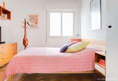 Quarto de casal tem piso de taco e cama de madeira com colcha e almofadas coloridas.