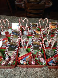 Christmas baskets for staff. Small Yankee candles with a gift card hot glued on candy canes hot glued together to make a heart and some fun  Christmas treats hidden inside. Small treat trays were bought in a three pack and red and green confetti was placed on the bottom. A nice little Christmas Thank you for teachers, staff, etc.
