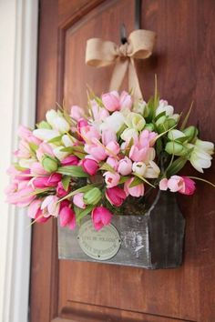 """Box O' Tulips – Reimagine Easter wreaths by hanging an overflowing springtime floral arrangement, perched in a perfectly distressed wooden box, from a ribbon on your door. Prettiest """"wreath"""" on the block? We'd say so. Click through for the full tutorial and for more easter wreaths."""