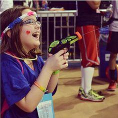A THON child having a blast with a water gun at the Jordan Center.