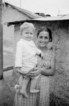 Φτώχεια και αισιόδοξα πρόσωπα. Χαμογελαστή νεαρή μητέρα στέκεται έξω από την παράγκα της. Στη αγκαλιά της ο μπέμπης λάμπει από ευτυχία. Προσφυγικός οικισμός στο Δουργούτι το 1955.... Dourgouti-N.Kosmoq 1955 (5)
