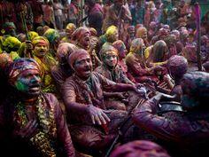 Hindu worshippers covered in coloured powder sing prayers during Lathmar Holi at a temple in Nandgaon, Uttar Pradesh.