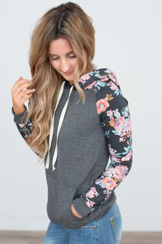 """Drawstring sweatshirt with a hood, kangaroo pocket, and floral contrast along the sleeves. Polyester/Rayon/Spandex. Hand wash. Measures 26"""""""" from shoulder to hem. Sleeves measure 22"""""""" long.Fits true"""