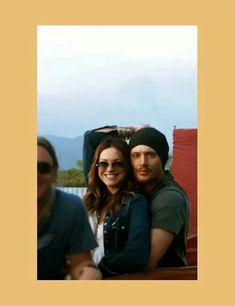 Jensen and Danneel candid. I love how she is reaching over her head for his.