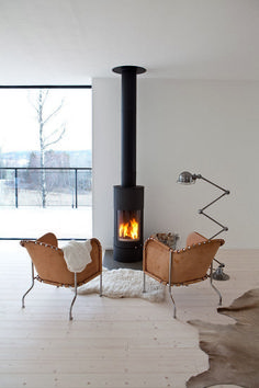 A tiny fireplace in the middle of an all-white living room. Animal furs, wide slat white wood floors - I'm in love.