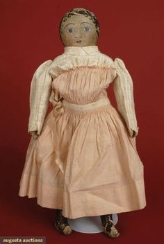 HAND PAINTED CLOTH DOLL, 1880s  Go Back Lot: 286 October 2007 Vintage Clothing & Textile Auction New Hope, PA Wearing original white eyelet trimmed pink cotton dress, white cotton pantaloons, white cotton petticoat & cream wool petticoat, 17.5