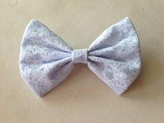 This beautiful bow is made of pale blue fabric and has a delicate white lace overlay throughout the entire bow! You are sure to feel super feminine and beautiful with this bow on! This bow can be made with a alligator clip, French barrette, or hair-tie.    Bow is shown in regular size. All bows c...