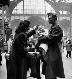 A wife and baby saying farewell to their serviceman husband at Pennsylvania Station during WWII, March 1943