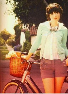 Zooey Deschanel: Mod moments wearing the nautical style button-pocketed shorts, ruffle-collared little white top and pastel 50's classic cardigan.  Even her bike is 50's...fabulous. <3