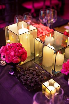 Pillar candles in varying size adds a soft glow to this deep purple setting. #WeddingCenterpiece