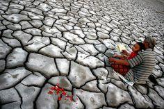 Un Indonésien et son fils prient sur les lieux d'une éruption volcanique qui a tué certains membres de leur famille en 2006, àSidoarjo sur l'île de Java, le 7 août.