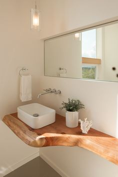A floating natural wood countertop features in this bathroom.