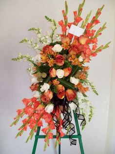A custom Sympathy Cross composed of Gladioli, Snapdragon, Akito & Coffee Break Roses, Alstroemeria, Stock, Aspid Leaf ribbons, & Scabiosa Pods. Accented with a Black chiffon ribbon.