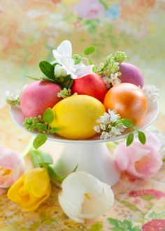 An arrangement of coloured eggs and fresh flowers on a pedestal dish makes an easy and festive table centrepiece for Easter. (Photos.com)