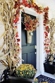 The corn stalks look like they're guarding the front door and the flowers keep them company