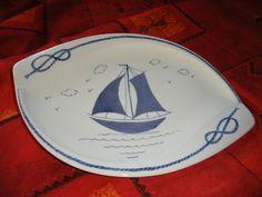 Ce plat de forme originale - forme ovale - (35 cm x 23 cm) est en porcelaine. Il est peint à la main et représente un bateau. Les bords sont ornés de nœuds marins. Tous les ob - 16793418