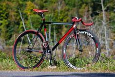 A beautiful red/black fixie bike.