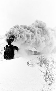 A freight train cutting through a snowy landscape.