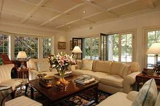 Comfortable living room with soft furnishings, fresh flowers, art and natural light through windows and doors all around. Beamed ceiling with recessed lights.
