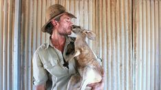 "Chris 'Brolga' Barnes, now the host of the popular BBC series ""Kangaroo Dundee,"" has dedicated his life to saving orphaned, abandoned, and ill kangaroos of the central Australian outbac…"