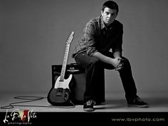 senior-guitarist-posing-by-guitar-and-speakers