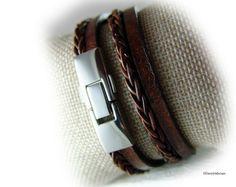 Dieses Lederarmband wird zwei Mal um das Handgelenk gewickelt. Geschlossen wird es mit einem Magnetverschluss aus Edelstahl.  Das flache Lederband ist aus geflochtenem tief dunkel braunem Nappaleder - das Foto mit dem Handgelenk ist aufgehellt. Ein fast identisches Armband in Schwarz finden Sie im Shop.   Schaut angezogen richtig cool aus....  Ein hochwertiges Lederarmband. Das Armband wird auf Maß angefertigt. Hierzu benötigen wir das exakte Maß (mit Nachkommastelle) - gemessen an der…