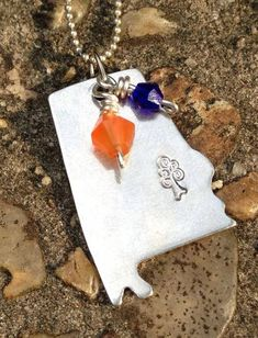 Toomer's Tree stamped Alabama necklace with wire wrapped blue glass bead and diamond cut carnelian.