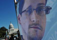 Μια εικόνα του Έντουαρντ Σνόουντεν στο πίσω μέρος από ένα πανό κατά τη διάρκεια μιας διαμαρτυρίας εναντίον της κυβερνιτικής επιτήρησης στις 26 Οκτωβρίου, 2013