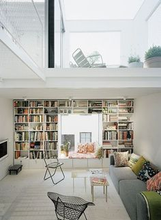 i like how the bookshelves were bulit around the window with storage space at the bottom AND a reading nook!