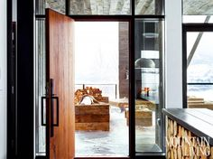 In our 2014 Home of the Year, a palette of glass, wood and steel at the front door, complemented by a half-wall that shows off a stack of logs, strikes the right balance of modern and rustic design. PHOTO BY Trevor Tondro