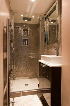 Tiny shower room. Glass mosaic walls. Bit too much 'bling' for me but good use of space