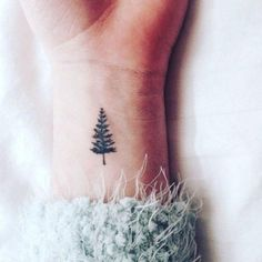 Get in the holiday spirit with this minimalist evergreen tree tattoo.