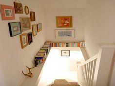 Dans cette cage d'escalier une poutre permet de créer une étagère pour le rangement des livres. Des cadres photos de toutes tailles colorent les murs blancs