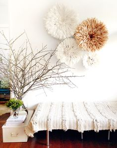 Juju hats as wall art in white room with branches