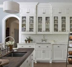 Dream kitchen design with white glass-front kitchen cabinets, marble tiles backsplash & counter tops, gooseneck bridge faucets, white kitchen island with Scandinavian walnut butcher block counter tops, blue walls and sink in kitchen island.