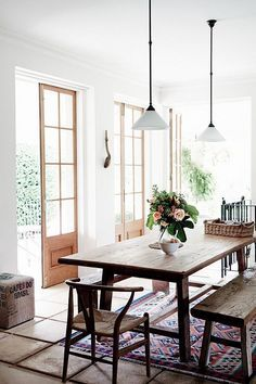 A bright and spacious dining room with a rustic wooden table.