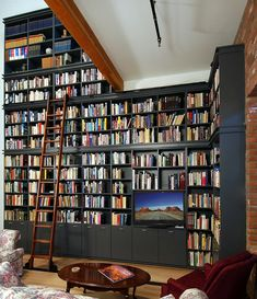 A giant black bookshelf with a wooden ladder