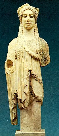 Greek Kore with almond-shaped eyes. The young woman is clad in a chiton and short himation, which buttons on the left shoulder. A band with a painted maeander ornamented the diadem on her hair and garments. Dated to 500 B.C. Acropolis Museum.