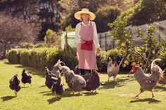 Full length portrait of a senior woman smiling at the camera outdoors in her sunny backyard, feeding her group of healthy free range chickens on her urban farm plot