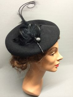 The Pearl! A large round felt fascinator with attached integral hairband. The Pearl is distinctively asymmetric  in shape with a thicker brim at the back and a circular dipped crown. Elegantly trimmed with a sleek feather pad, vintage button and long curved feather. Colour: Black #Fabhatrix #Edinburgh #Grassmarket #felt #fascinator #occasion
