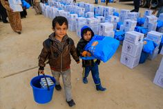 Ayman (left) and Khalid (right) carry supplies from a distribution point in the eastern part of Mosul city in Iraq on 9 December 2016. Photo: UNICEF/UN044148/Khuzaie