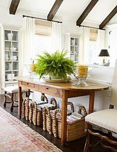 Off-white walls & furniture, hardwood floors, warm natural fiber shades, baskets and warm wood tone table