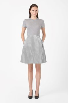 Based on the shape of a t-shirt, this cotton dress has a contrast pleated skirt in coated light-catching fabric. Fitted at the top and flaring towards the hem, it has a high round neckline, metal back zip fastening and in-seam side pockets.