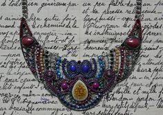 Collier fantaisie de type plastron vert/bleu/ocre/rouge/violet, composé de 3 belles pièces articulées en métal argenté, rehaussées de petits cabochons, perles, céramique et strass. Au centre, 1 joli palet en céramique ocre craquelé.