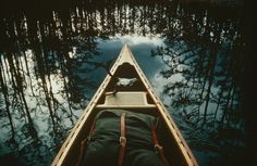 View of the bow of a canoe set against trees reflected in the still water, Georgia, 1981. Photo by Sam Abell via National Geographic Proof