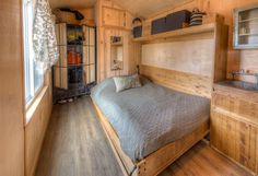 This rustic bedroom has a full wood paneled interior, including hide-away murphy bed and wardrobe. Click through for more photos of this tiny-home.